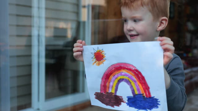4K Video of a Young Boy sticking his drawing on home window during the Covid-19 crisis