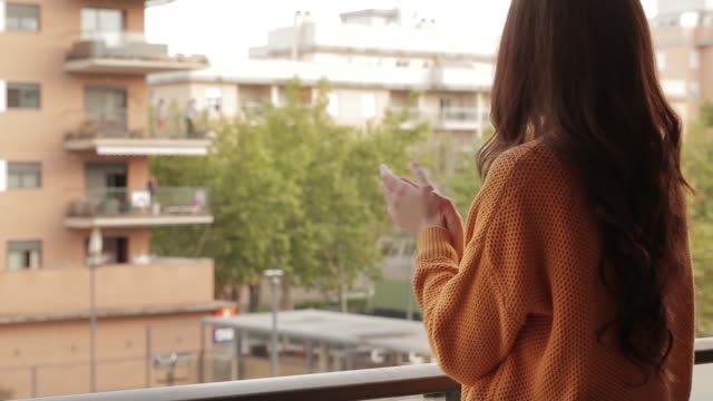 video of a young woman applauding on the balcony - rispetto video stock e b–roll