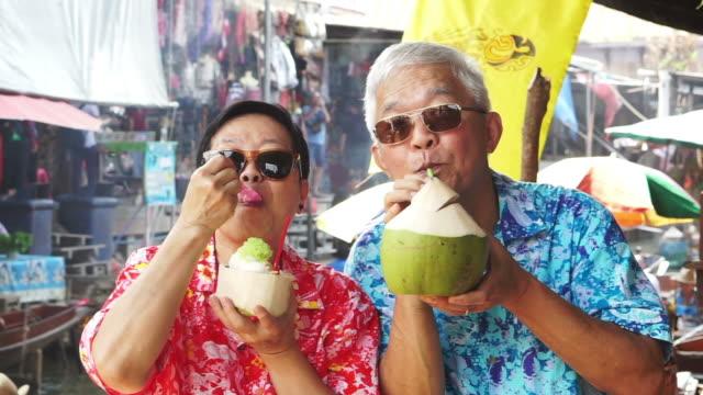 HD-video der asiatischen altes Paar reisen in Thailand Schwimmender Markt. Saft trinken frische Kokosnuss – Video