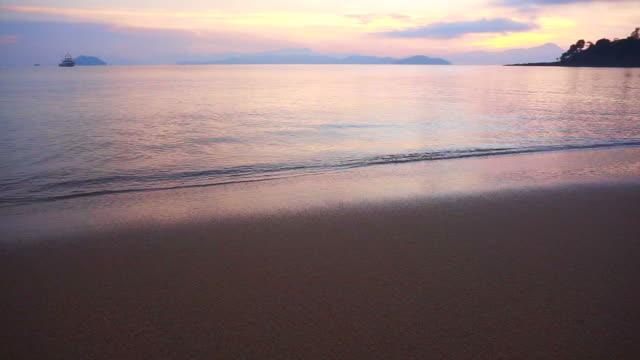 video av vackra soluppgången sand stranden och lugnt hav. rosa, lila och blå himmel - pink sunrise bildbanksvideor och videomaterial från bakom kulisserna