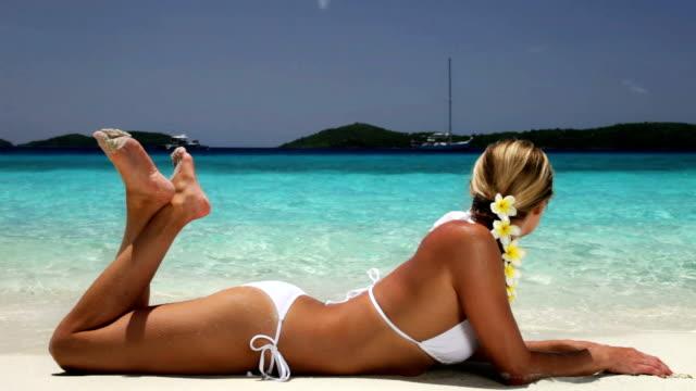 Vídeo de bikini mujer tomando el sol en la playa del caribe - vídeo