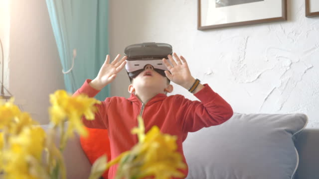 Video of boy exploring virtual reality and playing games in 4k slow motion High quality video of boy wearing virtual reality glasses and playing games in 4k in slow motion 60fps vr stock videos & royalty-free footage