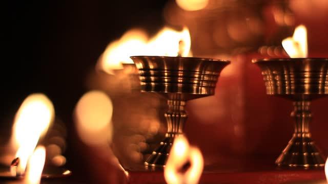 vídeos de stock, filmes e b-roll de vídeo de velas do altar budista no festival religioso de lâmpadas de manteiga 108 em templos e mosteiros. vista cênica tranquila de lâmpadas a óleo e chama balançando para orar em embarcação metálica - buda