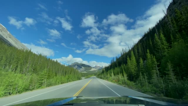 4k pov video of car driving on empty highway in banff national park, canada - passo montano video stock e b–roll