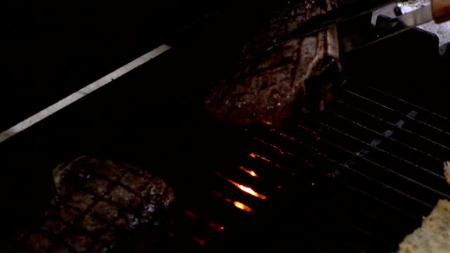 Video of checking steaks on the grill-real slow motion video