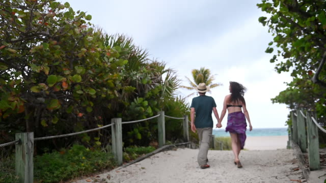 video of couple holding hands walking to the beach on vacation - body positive video stock e b–roll