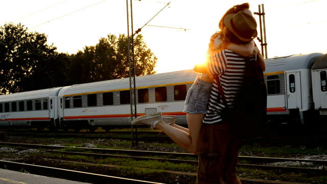 Video of couple hugging on train station Portrait of beautiful redhead woman with handsome boyfriend in casual clothing traveling for summer holiday railroad station platform stock videos & royalty-free footage