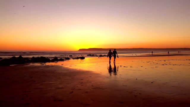 Video of couple walking at the sunset in real slow motion