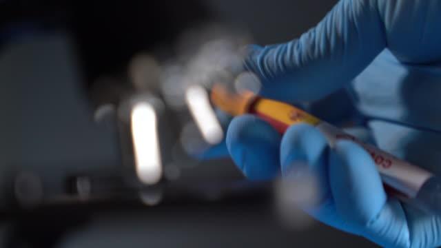 hd-video av covid-19 medicinskt provrör med flagga spanien i människohand med kirurgisk handske - test tube bildbanksvideor och videomaterial från bakom kulisserna