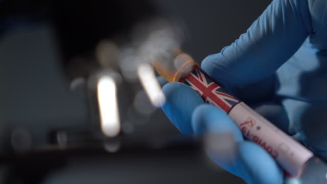 HD Video Of Covid-19 Medical Test Tube With Flag Of UK In Human Hand With Surgical Glove video