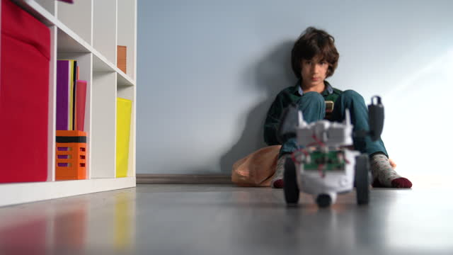 Video Of Elementary Schoolboy Playing With Toy Robot At Home video