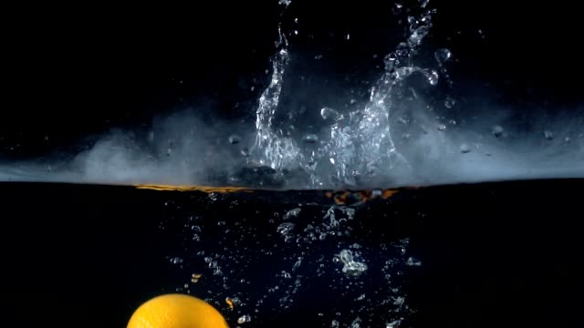 video of falling granadilla in the water with smoke - passiflora video stock e b–roll
