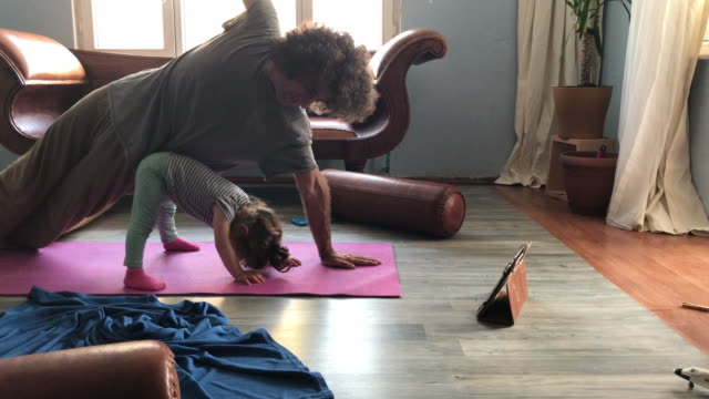 4K Video Of Father Doing Yoga Exercises While Baby Daughter Playing Around video
