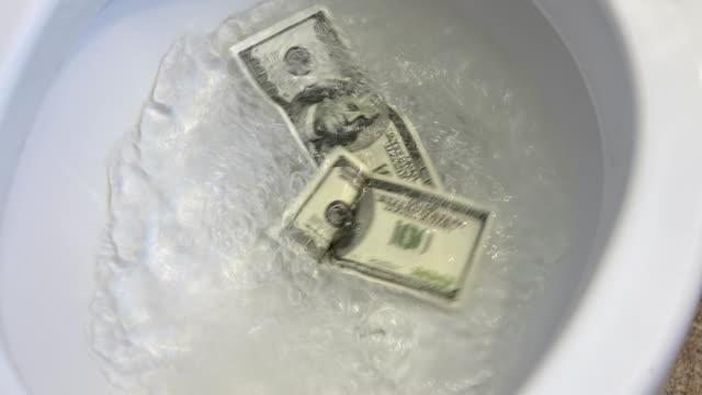 Video of flushing dollars in toilet bowl in 4K video