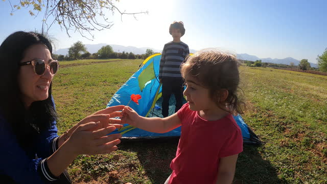 4K Video Of Girl Giving Flowers To Her Mother During Camping In Nature