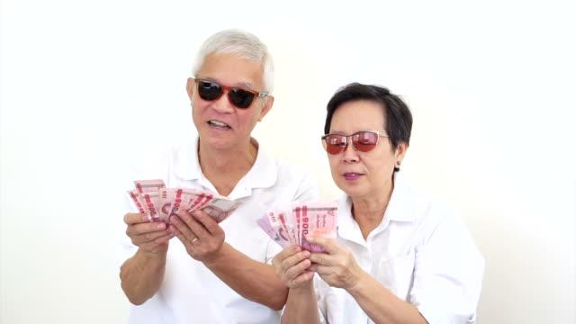 Vídeo de feliz pareja Senior asiática e intensos. Ganó de lotería o el Casino efectivo - vídeo