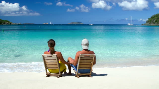 stockvideo's en b-roll-footage met video of honeymoon couple sitting in chairs at a beach - caraïbische zee