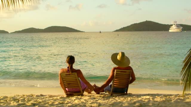 video of honeymoon couple watching sunset at a Caribbean beach video