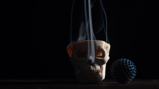 vídeos y material grabado en eventos de stock de vídeo 4k de cráneo humano y un objeto en forma de virus en un escritorio de madera - halloween covid