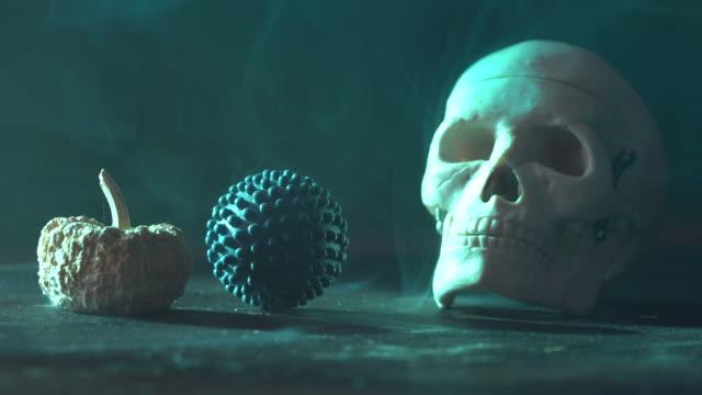 vídeos y material grabado en eventos de stock de vídeo 4k de cráneo humano, calabaza seca y un objeto en forma de virus en el escritorio de madera - halloween covid