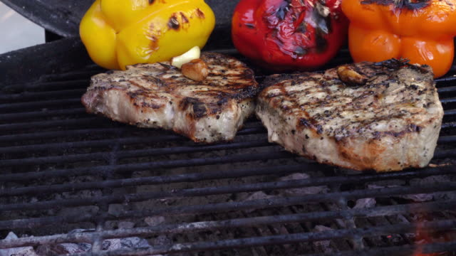 a video of ketogenic grilled bone-in pork chops, fully cooked with colorful roasted peppers, with hot, grill with flames - filetto video stock e b–roll