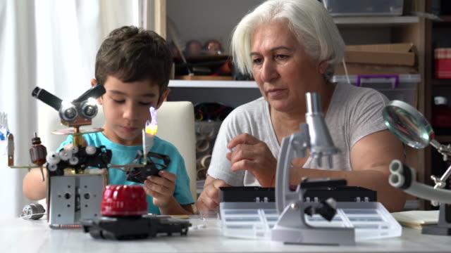 uhd video of little boy and grandmother building robot - манипулятор робота производственное оборудование стоковые видео и кадры b-roll