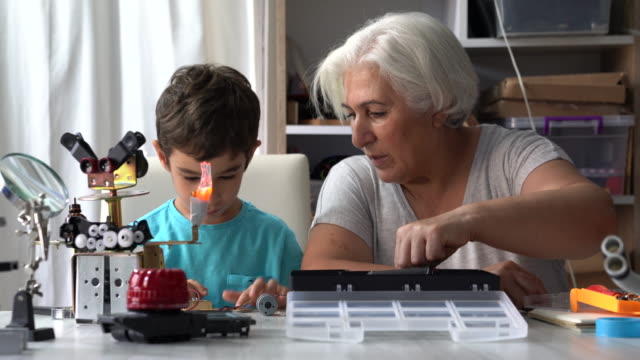 UHD Video Of Little Boy And Grandmother Building Robot video
