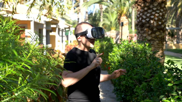 Video of man exploring virtual reality in tropical resort in 4k slow motion video