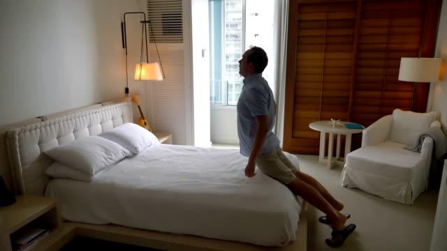 vídeos de stock e filmes b-roll de video of man jumping on the bed in slow motion - cansado