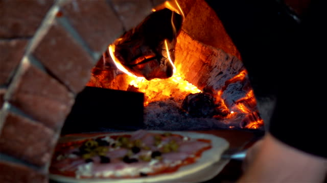 video of man putting pizza to brick oven in real slow motion - italian food stock videos & royalty-free footage