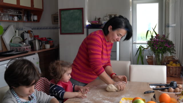 4K Video Of Mother And Children Cooking Pizza In Kitchen video