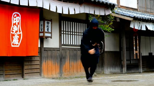 Video of ninja warrior in old Japanese village Portrait of ninja in empty old street in traditional Japanese village. Footage taken with Nikon D800 and 50mm lens. Location: Kyoto, Japan ninja stock videos & royalty-free footage
