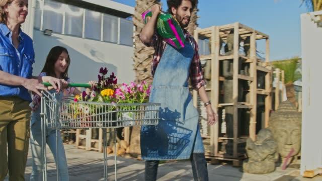 Vidéo du travailleur jardin pépinière clients chargement des plantes fleuries pour la voiture - Vidéo