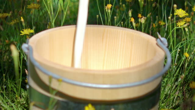 Video of pouring milk into wooden bucket-real slow motion video