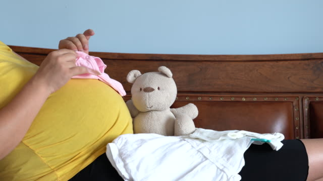 UHD Video Of Pregnant Woman Folding Baby Clothes video