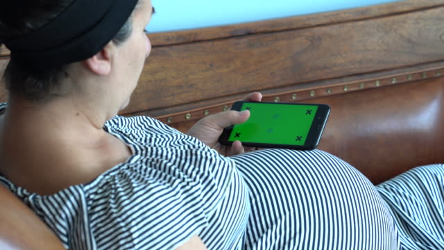 UHD Video Of Pregnant Woman Using Mobile Phone With Green Screen video