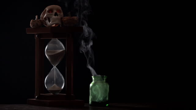 4K Video Of Pumpkin, Human Skull, Hourglass And Poison Bottle In Dark