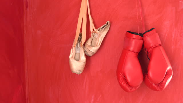 4K Video Of Red Boxing Gloves And Pointe Shoes Hanged On Red Wall video