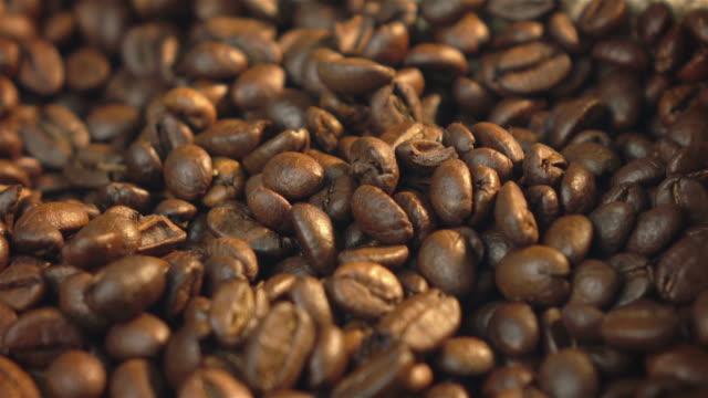 video von rotierenden kaffeebohnen in 4 k - rohe kaffeebohne stock-videos und b-roll-filmmaterial