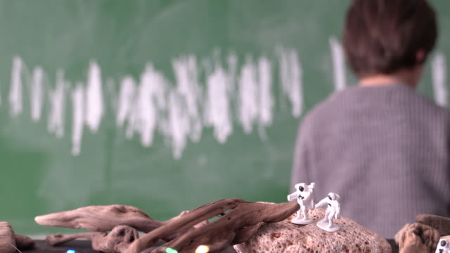 UHD Video Of School Boy Playing With Scientific Toys In Front Of Green Chalkboard video