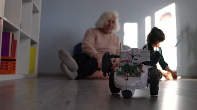 Video Of Schoolboy Playing With Toy Robot In Living Room While Grandmother Is Watching video