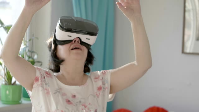 Video of senior woman exploring virtual reality in 4k slow motion video