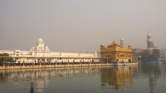 vídeos de stock, filmes e b-roll de vídeo de peregrinos siques no templo de ouro ao entardecer durante a celebração do dia em dezembro em amritsar, punjab, índia. harmandir sahib é o local mais sagrado do peregrino para os sikhs. - característica arquitetônica