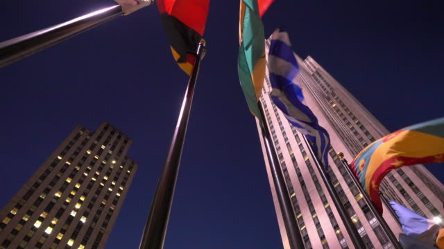 Video of some flags moved by the wind in the foreground and the Rockefeller building in the background in Manhattan, New York.