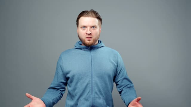 Video of surprised young man in blue sweatshirt Video of blond man in blue sweatshirt with different emotions on gray background sweatshirt stock videos & royalty-free footage