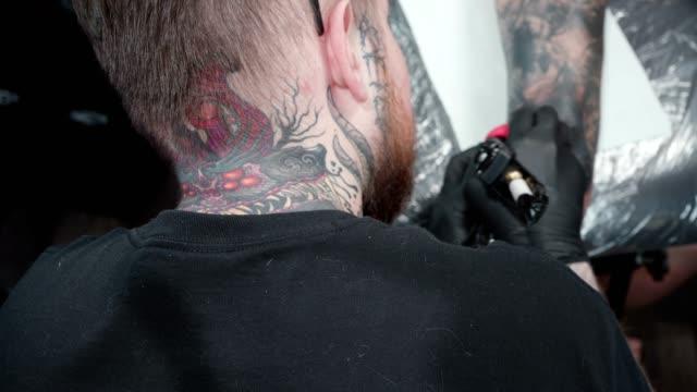 video von tätowierer immer tattoo auf ellenbogen im salon, ansicht - menschliches gelenk stock-videos und b-roll-filmmaterial