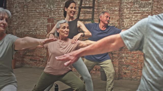 video av lärare med grupp seniorer träning i yogaklass - mature women studio grey hair bildbanksvideor och videomaterial från bakom kulisserna