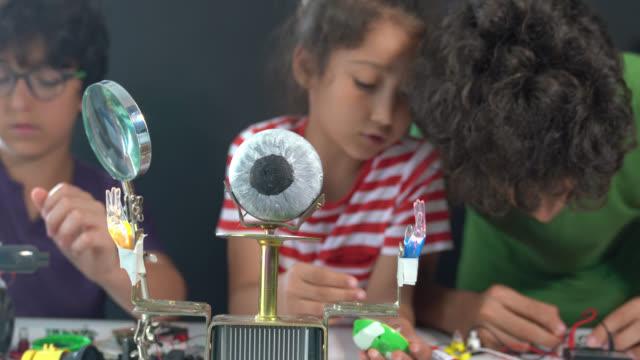 4K Video Of Three Children Working On Robotics In Front Of Blackboard video