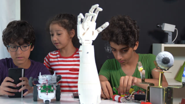 4K Video Of Three School Children Trying To Build A Robotic Arm video