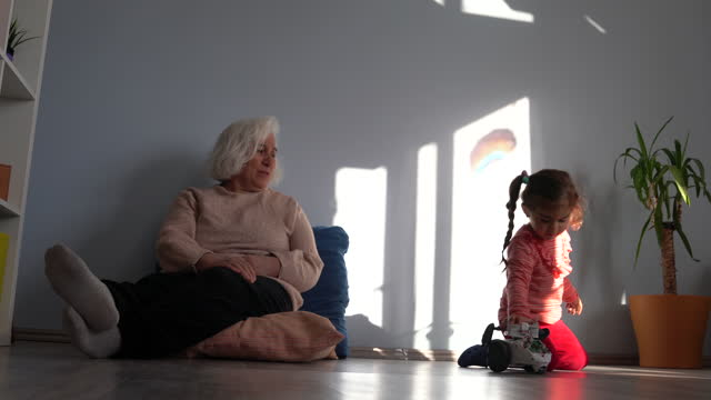 Video Of Toddler Girl Playing With Toy Robot In Living Room While Grandmother Is Watching video
